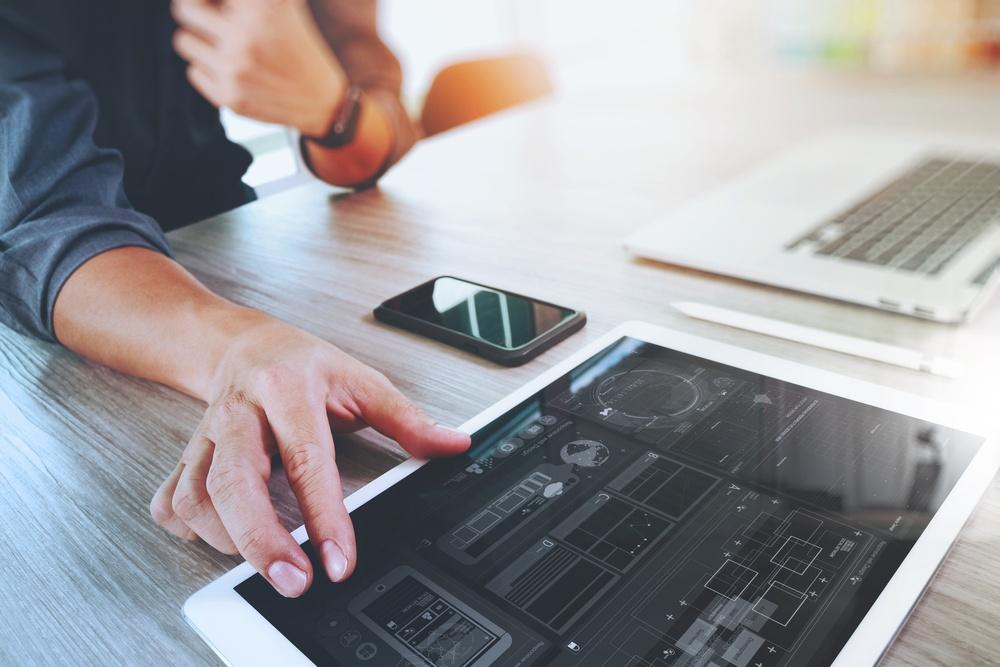 Website designer working digital tablet and computer laptop with smart phone and graphics design diagram on wooden desk as concept.jpeg